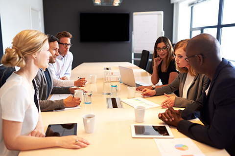 This is a stock photo. A diverse group of people conducting a meeting in a board room.